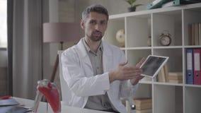 Портрет красивого человека в белой робе смотря в планшете показа камеры с изображением рентгеновского снимка легких Умелый сток-видео