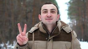 Портрет красивого человека в куртке показывает жест победы на камере Человек стоит в лесе зимы видеоматериал