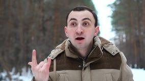 Портрет красивого человека в куртке показывает жест успеха на камере Человек стоит в лесе зимы видеоматериал