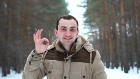 Портрет красивого человека в куртке показывает одобряет жест на камере Человек стоит в лесе зимы видеоматериал