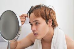 Портрет красивого человека смотря себя в зеркале и brushi Стоковые Изображения
