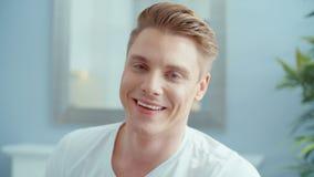 Портрет красивого человека усмехаясь к камере, внутри помещения видеоматериал