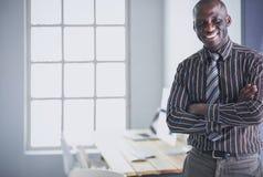 Портрет красивого черного бизнесмена стоя в офисе Стоковые Изображения