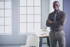 Портрет красивого черного бизнесмена стоя в офисе Стоковое Фото