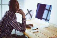 Портрет красивого черного бизнесмена стоя в офисе Стоковое Изображение