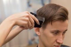 Портрет красивого человека в парикмахерскае парикмахер работая с электробритвой стоковые изображения