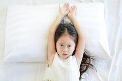 Портрет красивой азиатской девушки ребенка лежа на кровати над взглядом стоковая фотография