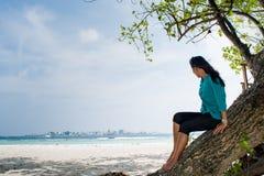 Портрет красивой азиатской девушки на дереве около пляжа смотря океан Стоковое Фото