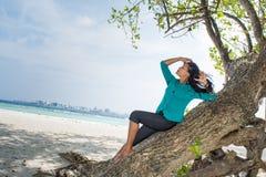 Портрет красивой азиатской девушки на дереве около пляжа Стоковое Изображение