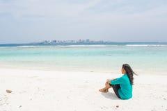 Портрет красивой азиатской девушки сидя на пляже с городом на предпосылке Стоковое фото RF