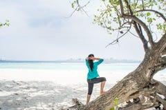 Портрет красивой азиатской девушки стоя на дереве около пляжа смотря океан Стоковая Фотография RF