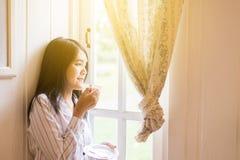 Портрет красивой азиатской женщины держит чашку кофе и смотрит что-то на окне дома в утре, счастливый и smil стоковые фотографии rf