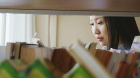 Портрет красивой азиатской серьезной студентки стоя близко полка с книгами в большом lighty учебнике удерживания библиотеки акции видеоматериалы