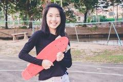 Портрет красивой азиатской усмехаясь девушки держа скейтборд на y Стоковая Фотография RF