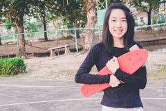 Портрет красивой азиатской усмехаясь девушки держа скейтборд Стоковое Изображение