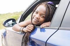 Портрет красивой африканской женщины смотря вне окна автомобиля Стоковые Изображения