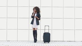Портрет красивой Афро-американской коммерсантки говоря телефоном на белой текстурированной предпосылке стены Чернокожая женщина сток-видео