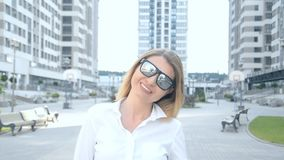 Портрет красивой белокурой девушки в солнечных очках в современном городе на заднем плане акции видеоматериалы