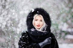 Портрет красивой белокурой девушки в теплой меховой шыбе внешней в снежном лесе Стоковое фото RF
