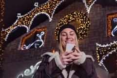 Портрет красивой белокурой девушки используя умный телефон перед Стоковые Изображения RF