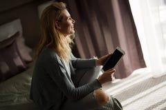 Портрет красивой белокурой женщины используя таблетку Стоковые Изображения