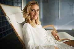 Портрет красивой белокурой женщины ослабляя на стуле Стоковая Фотография