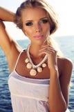 Портрет красивой белокурой девушки при яркий состав представляя на пляже Стоковое фото RF