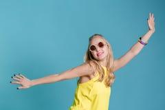 Портрет красивой белокурой женщины в солнечных очках и желтых танцах рубашки на голубой предпосылке беспечальное лето Стоковая Фотография RF