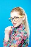 Портрет красивой белокурой женщины при Ponytail нося красочную рубашку на голубой предпосылке Усмехаясь девушка в Eyeglasses Стоковые Изображения
