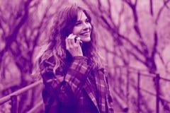 Портрет красивой бизнес-леди с вьющиеся волосы используя умный телефон outdoors стоковые изображения rf
