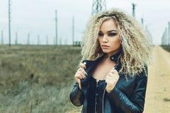 Портрет красивой блондинкы в кожаной куртке с составом и стилем причёсок стоковые изображения rf