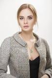 Портрет красивой блондинкы бизнес-леди в черном платье, куртке на серой предпосылке Стоковая Фотография
