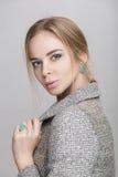 Портрет красивой блондинкы бизнес-леди в черном платье, куртке на серой предпосылке Стоковое Изображение