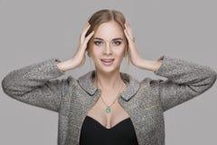 Портрет красивой блондинкы бизнес-леди в черном платье, куртке на серой предпосылке Стоковое фото RF