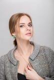 Портрет красивой блондинкы бизнес-леди в черном платье, куртке на серой предпосылке Стоковые Фотографии RF