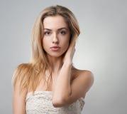 Портрет красивой блондинкы на серой предпосылке Стоковое Изображение RF