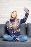 Портрет красивой блондинкы принимая selfie с ее умным телефоном дома Стоковое Изображение RF