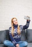 Портрет красивой блондинкы принимая selfie с ее умным телефоном дома Стоковая Фотография