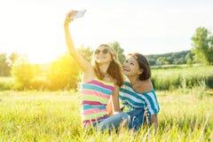 Портрет красивой взрослой матери и ее девочка-подростка дочери делая selfie используя умный телефон и усмехаться Стоковая Фотография RF