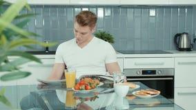 Портрет красивой газеты чтения человека на таблице завтрака сток-видео