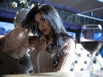 Портрет красивой девушки брюнета сидя на таблице со стеклом красного  стоковые изображения