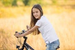 Портрет красивой девушки брюнет сидя на велосипеде на поле стоковые изображения