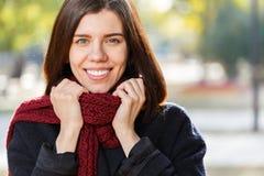 Портрет красивой девушки в парке осени в красном шарфе, держа дальше к шарфу Стоковые Изображения