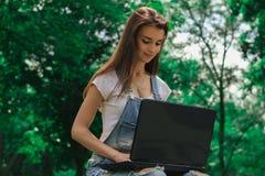 Портрет красивой девушки в парке против фона деревьев с компьтер-книжкой Стоковая Фотография RF