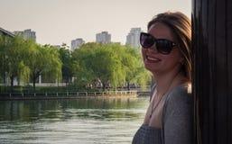 Портрет красивой девушки в солнечных очках стоя около деревянного штендера на заходе солнца Стоковые Изображения