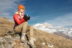 Портрет красивой девушки в шляпе и солнечных очков с кружкой в ее руках выпивает кофе или чай пока сидящ дальше стоковое изображение rf