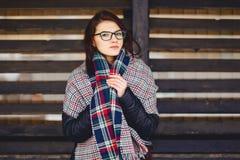 портрет красивой девушки в eyeglasses и шарфе против w Стоковая Фотография