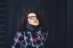 портрет красивой девушки в eyeglasses и шарфе против w Стоковые Фото