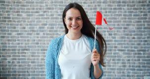 Портрет красивой девушки держа канадский флаг на предпосылке кирпичной стены акции видеоматериалы