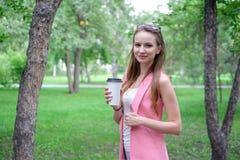Портрет красивой девушки идя на парк Держать на вынос питье в одной руке Стоковая Фотография RF